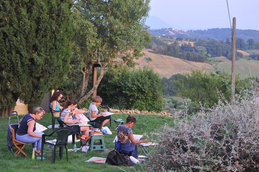 Kursteilnehmer sitzen im Garten und zeichnen.